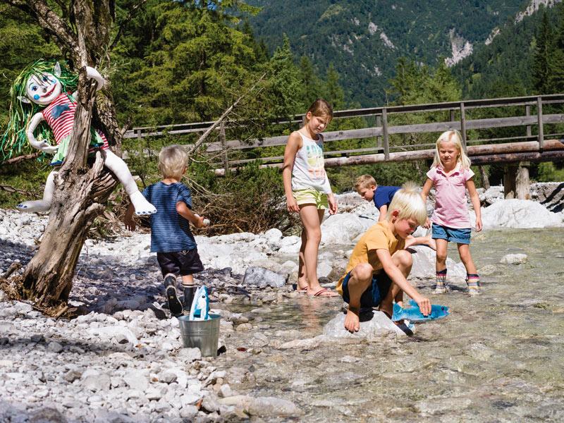 kinder spielen bach sommerurlaub